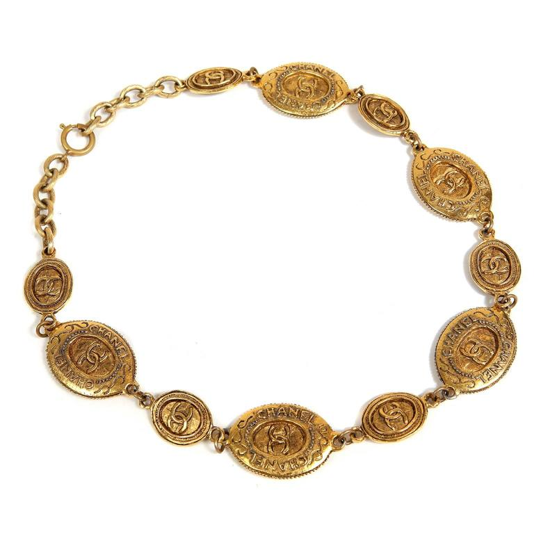 Chanel Oval Coin Necklace- PRISTINE   Worn with everything from t- shirts to gowns, this elegant piece is a must have for any collection.  Antiqued gold oval coins in alternating sizes.  Interlocking CC design.  Adjustable length clasp closure.