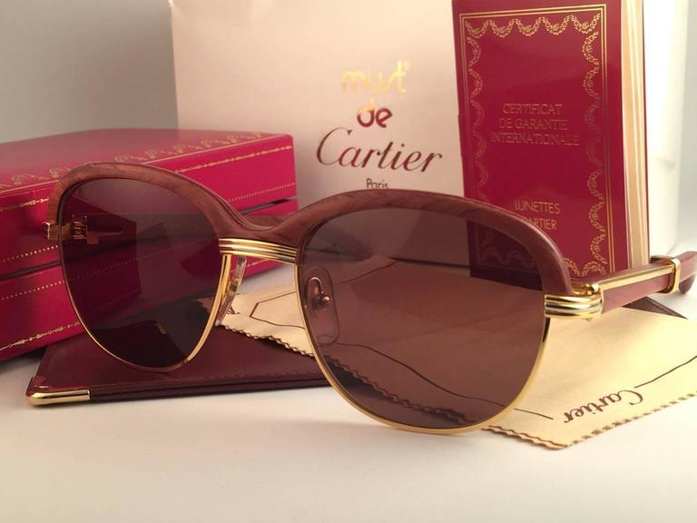 Original New 1990 Cartier Malmaison Palisander hardwood sunglasses with honey brown(uv protection) lenses.  Front and sides in yellow and white gold and has the famous wooden front. Temples are also Palisander combined with gold.  Amazing