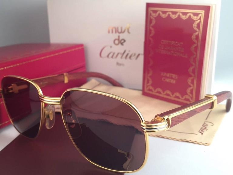 New 1990 Cartier Full Set Monceau Palisander Hardwood sunglasses with new solid honey brown (uv protection) lenses.  Frame with the front and sides in yellow and white gold and has the famous hardwood with gold accents temples.  Amazing