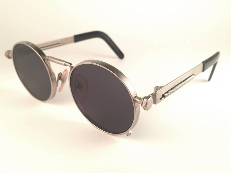 New Jean Paul Gaultier 56 8171 round gunmetal silver matte frame.  Flat smoke grey lenses that complete a ready to wear JPG look.  Amazing design with strong yet intricate details. Design and produced in the 1900's. New, never worn or displayed. A