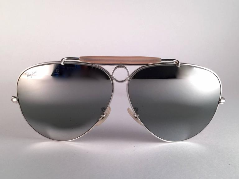 New Vintage Ray Ban Shooter White Gold 62mm with double mirror lenses.  B&L etched twice in both lenses.   Comes with its original Ray Ban B&L case.   A seldom piece in new, never worn or displayed condition.
