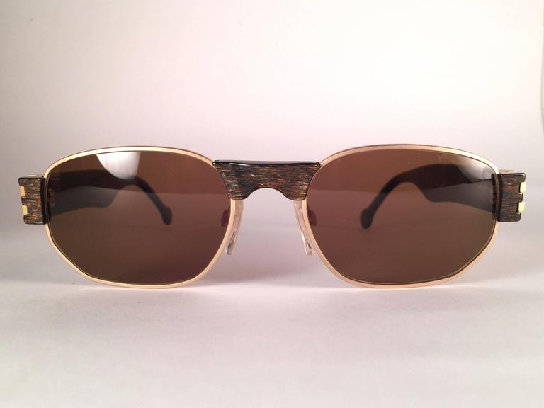 New, never worn Karl Lagerfeld matte gold with translucent stripes frame holding a spotless pair of solid brown lenses.   Designed and produced in 1990's.  New, never worn or displayed. Made in Austria.