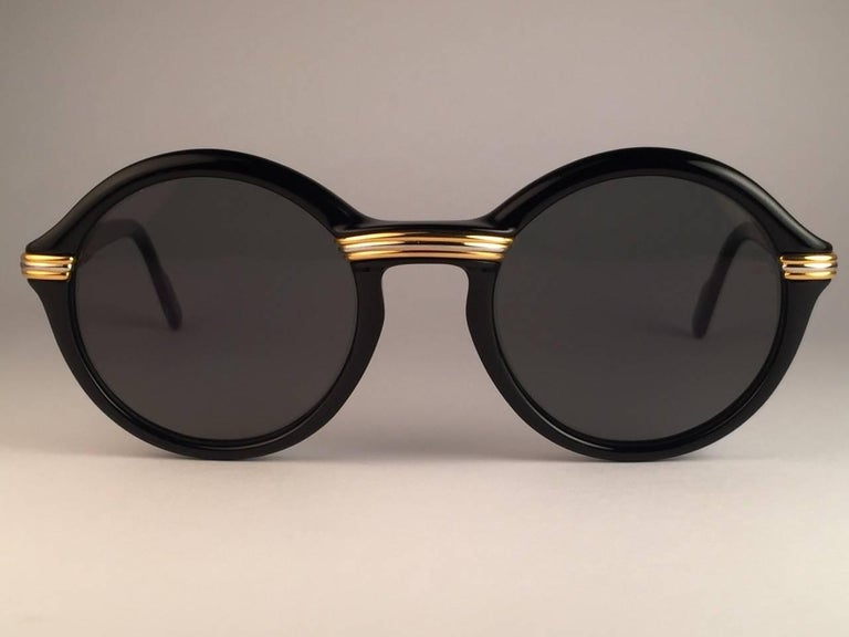 New 1991 Original Cartier Cabriolet Art Deco Black & Gold Sunglasses with slight gold mirror ( uv protection ) lenses Frame has the famous real gold and white gold accents in the middle and on the sides.  All hallmarks. Cartier gold signs on the
