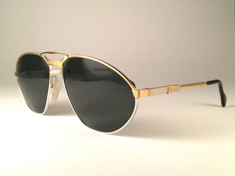 New Vintage Zeiss Competition Sunglasses in Silver and gold frame holding a pair of grey lenses. This item may show light sign of wear due to storage.   Made in West Germany.