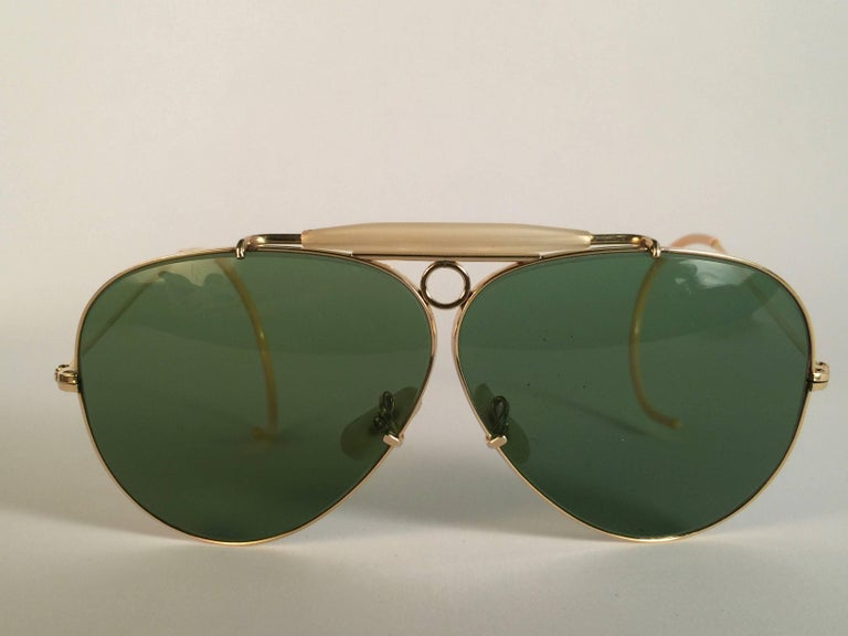 Superb pair Of Ray Ban Classic Outdoorsman 62Mm with 12K gold filled frame.  Gold filigree temples1950's USA Made by Bausch and Lomb. Original True Green RB3 B&L lenses. Frame straight as an arrow with mother of pearl browser. All the hallmarks.