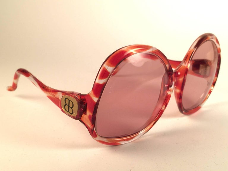 New Vintage Balenciaga clear and amber oversized frame holding a spotless pair of light rose lenses.  Never worn or displayed. This pair could show minor sign of wear due to storage.  Designed and produced in France.