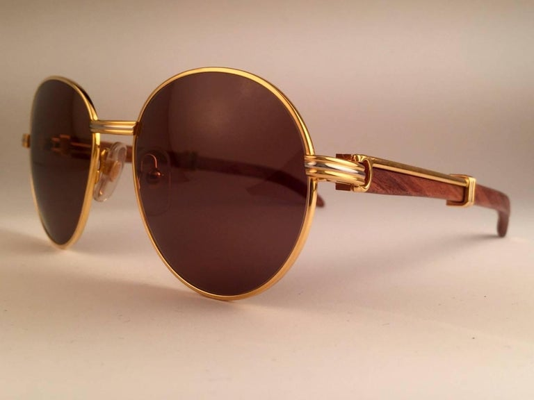 New original 1990 Cartier Bagatelle Wood Sunglasses from the coveted Precious Wood series with palisander wood temples and honey brown (uv protection) lenses.  The frame has the front and sides in yellow and white gold.  All hallmarks. gold Cartier