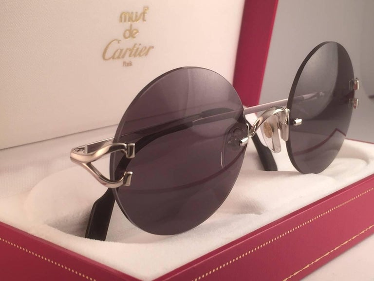 New 1990 Cartier Madison unique rimless sunglasses with grey (uv protection) lenses.  Frame with the front and sides in Platine.  Cartier Platine signs on the onyx black ear paddles.  These are like a pair of jewels on your nose.  Beautiful design