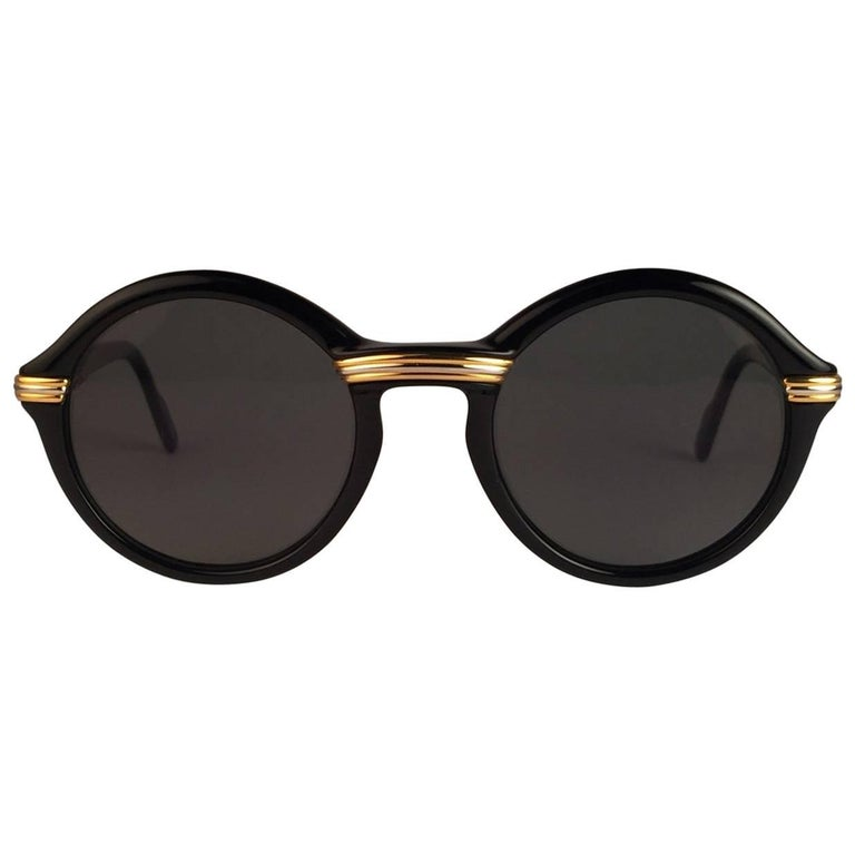 New 1991 Original Cartier Cabriolet Art Deco Black & Gold Sunglasses with gold ( uv protection ) lenses Frame has the famous real gold and white gold accents in the middle and on the sides.  All hallmarks. Cartier gold signs on the earpaddles. Both