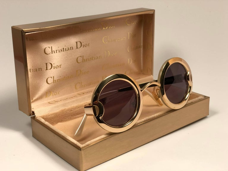 Ultra rare pair of Christian Dior Sunglasses. Round Gold plated sunglasses backed by two mother of pearl acetate circles. CD written on the gold temples.  This is a rare piece. Limited edition, with serial number on the temple.  Please notice that
