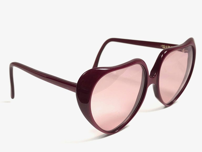 Superb & rare pair of Oliver Goldsmith sunglasses.   Oversized burgundy heart shaped frame holding a pair of spotless lenses.     New, never worn or displayed. This pair may have minor sign of wear due to storage.  Handmade in England.