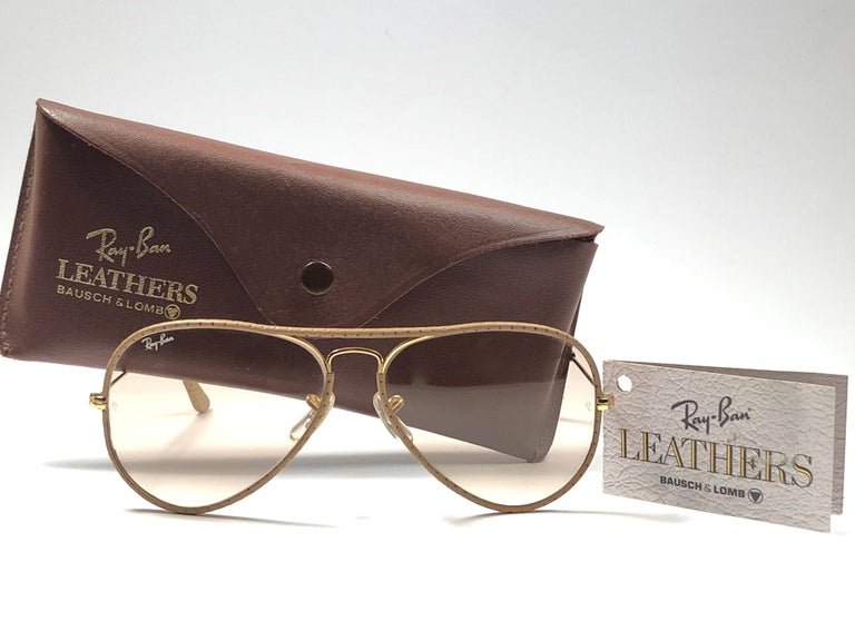 New Vintage Ray Ban Leathers 58mm in tan perforated leather with gold metal combination frame sporting brown changeable lenses.  Comes with its original Ray Ban B&L case with minor sign of wear due to storage.  Rare and hard to find in this new,