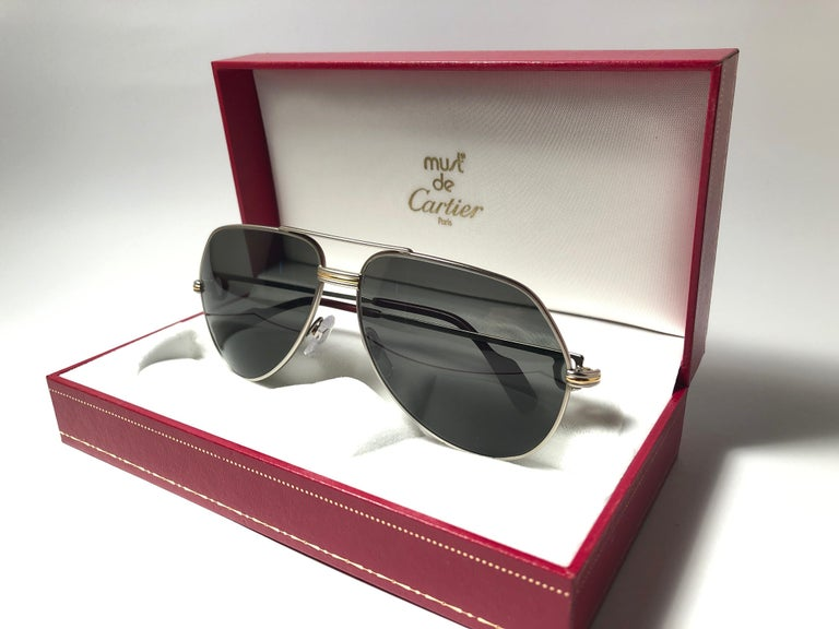 Vintage Cartier Aviator Vendome 59MM titanium sunglasses with grey (uv protection) Lenses.  Frame is with the famous Vendome stripes on the front and sides in yellow and white gold.  All hallmarks.  Red enamel with Cartier gold signs on the ear