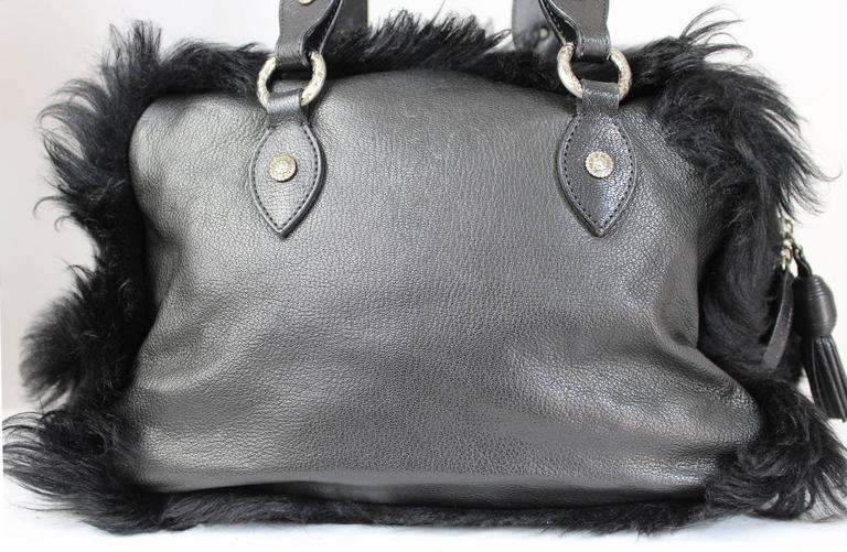 Vintage Moschino black leather and fur handbag 1990s. The fur is all around the bag and on the front pocket. The pocket flap frontal features a large logo Moschino. A large M two horns and two big leaves outline the logo. Inside, one zip pocket, and