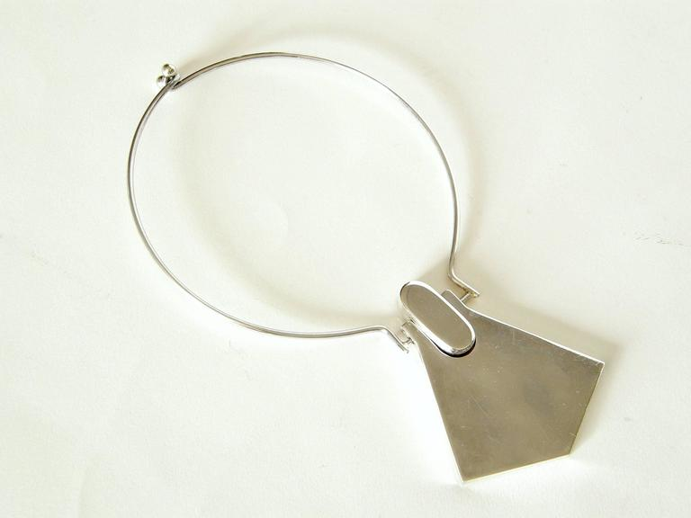 This sterling neck ring with integrated geometric pendant has a space age style. The two part pendant has a nice dimensionality, as the oval part at the top is deeper than the flared, angled part below it.   Please contact us if you have any