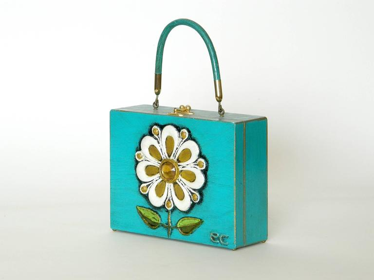 Cheerful, handmade papier mache box bag with jeweled flower by Enid Collins. It rests on little brass button feet.