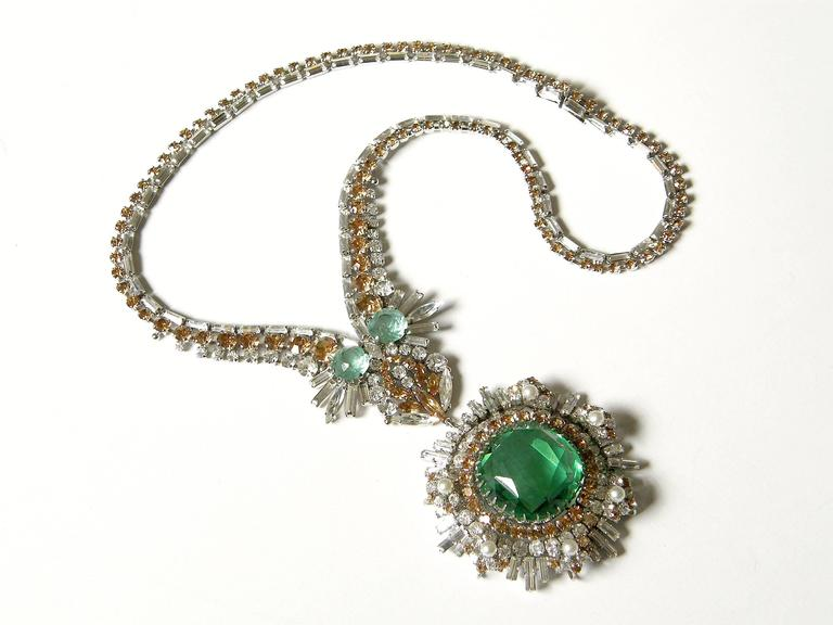 This exceptional rhinestone necklace features a huge, light green stone in the center of the pendant. It's surrounded by radiating faux diamonds, citrines, and pearls. The style is like that of the best of fine jewelry makers. The rhinestones are