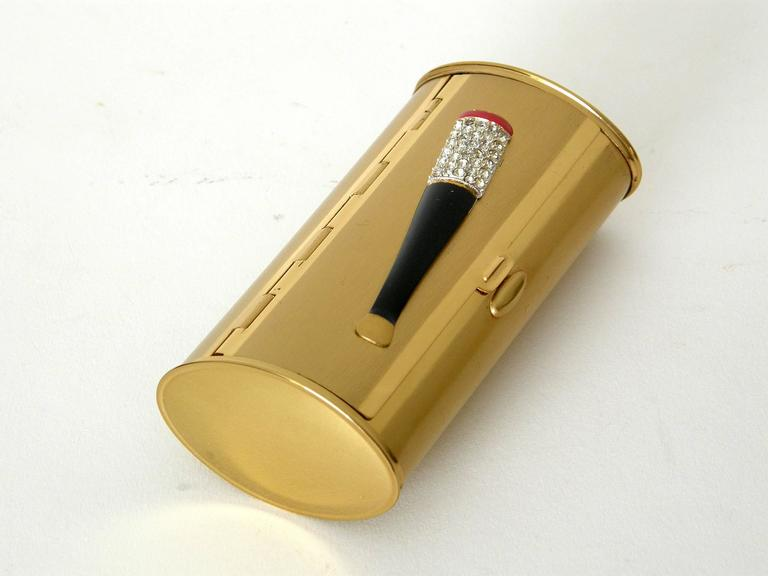 "This cigarette case is a wonderful novelty accessory. It has a glamorous, bejeweled ""lit"" cigarette in a cigarette holder on the lid that's made like a piece of enameled rhinestone jewelry. The oval body has a satin gold finish with polished gold"