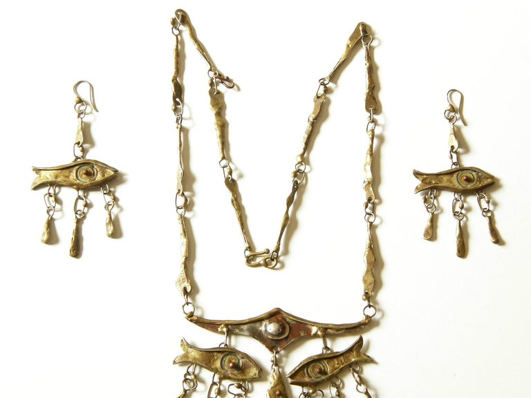 This unique necklace and earrings set was made by Mexican artist Armando Lozano Ramirez. The fish motif is utilized to great effect, creating an abstract face in the necklace. The dangling eyes and nose are fish, and a tiny puckered mouth is