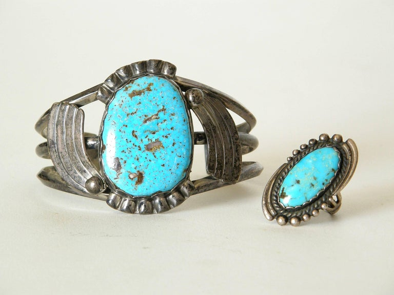 These c. 1940s or 1950s sterling cuff bracelet and ring are set with turquoise. The stones have scalloped bezel settings that are flanked by tapering bands that create a feeling of movement like shooting stars or a spinning effect. The ring and