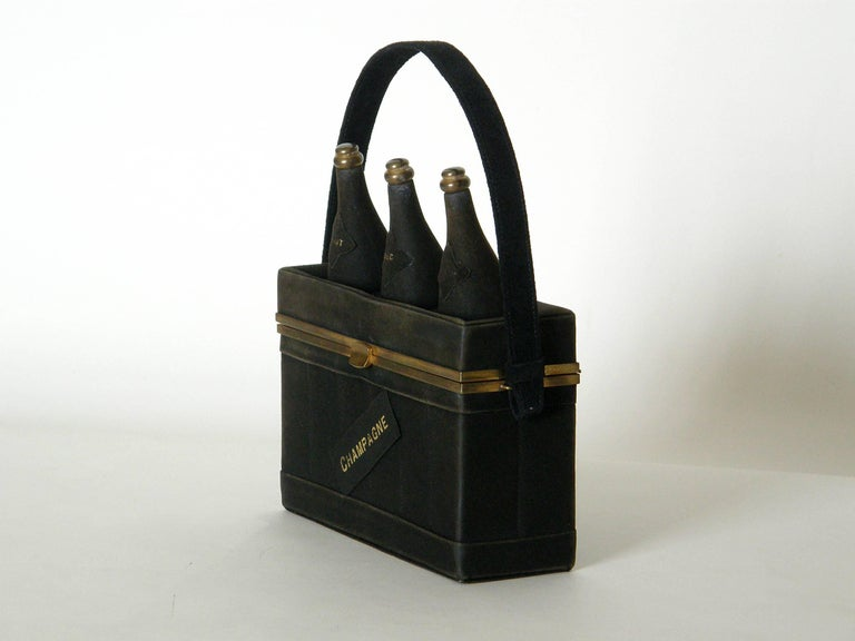 This wonderful figural handbag is shaped like a wooden crate with 3 champagne bottles sticking out of the top. Made from a fine black suede, the crate has a label on the front stamped