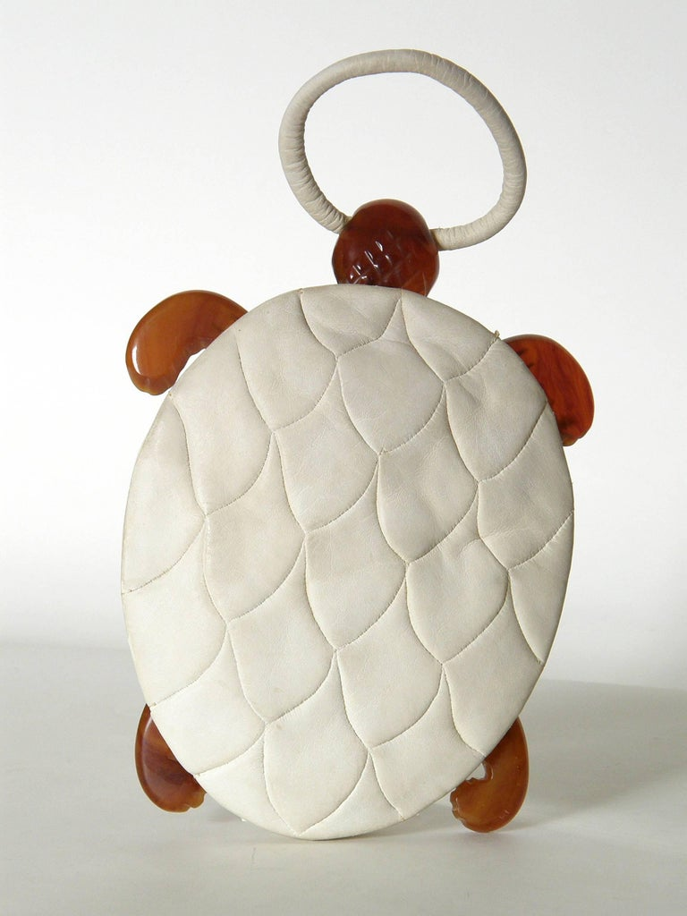 This adorable turtle shaped handbag has wonderful details. The body / shell of the turtle is done in soft, cream colored (kid?) suede. The back is pieced to resemble the pattern and texture of a turtle shell with plates. The belly of the turtle is
