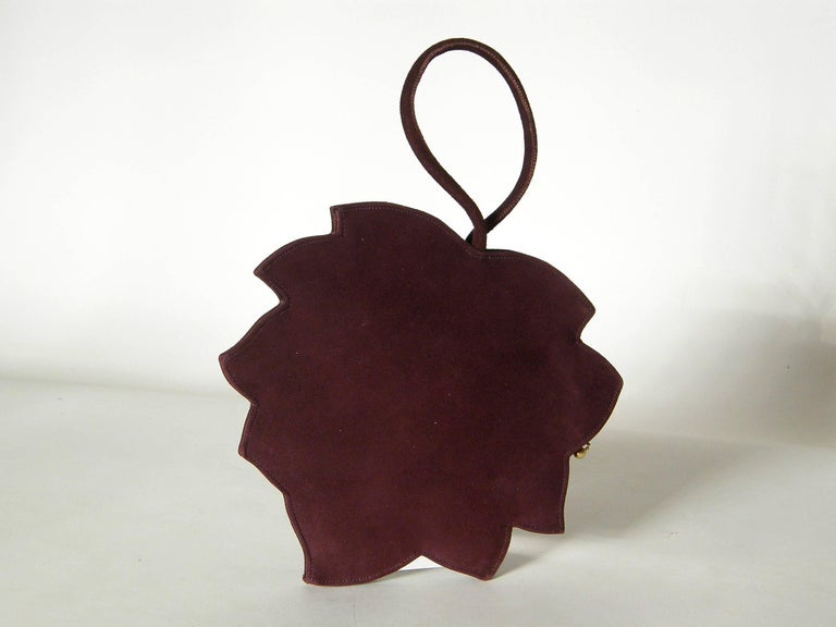 This marvelous figural handbag shaped like a realistic leaf is made of a gorgeous, aubergine colored suede with raised, stitched
