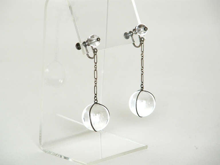 """""""Pools of light"""" un-drilled rock crystal and sterling earrings. These pieces create beautiful and dramatic optical effects because of the way the orbs absorb and refract light. They are said to have mystical and healing properties and to ward off"""
