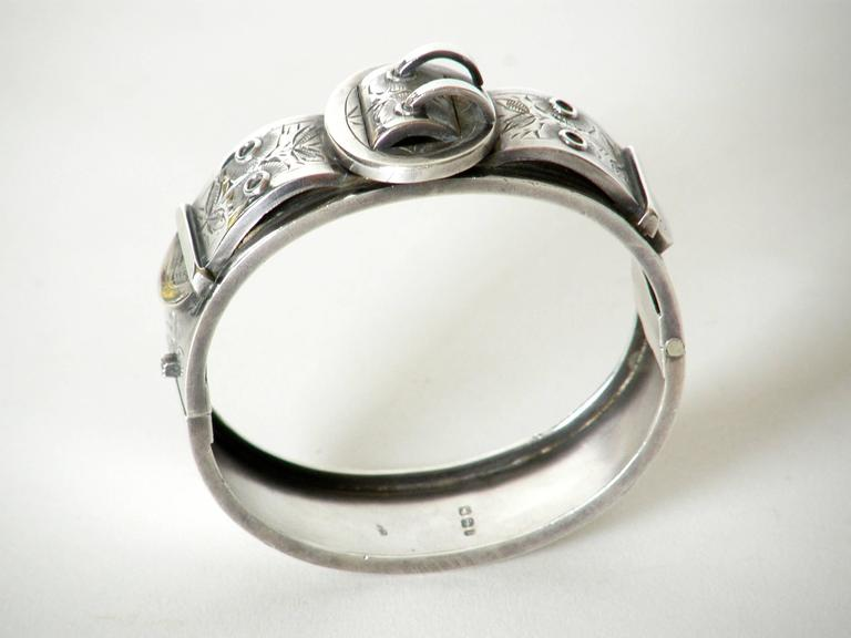 """Victorian sterling hinged bangle bracelet with buckle motif. The three dimensional form of the applied """"buckle"""" is hand engraved with delicate floral designs.  The bracelet opening measures approximately 2"""" x 2.19"""". Measurements given below are"""