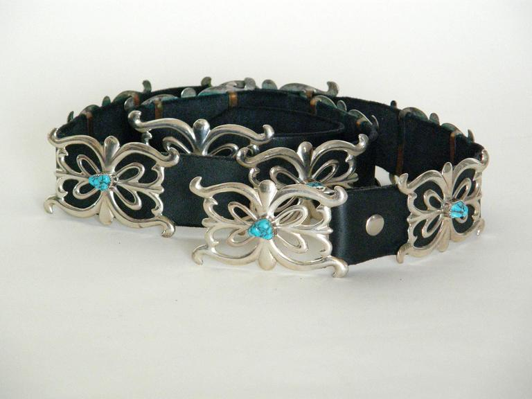 Black leather belt featuring ten sandcast sterling conchos, including the buckle, that are set with turquoise stones. This piece is probably Navajo. It has not been worn. It's never had holes punched in the leather, so they can be custom placed to