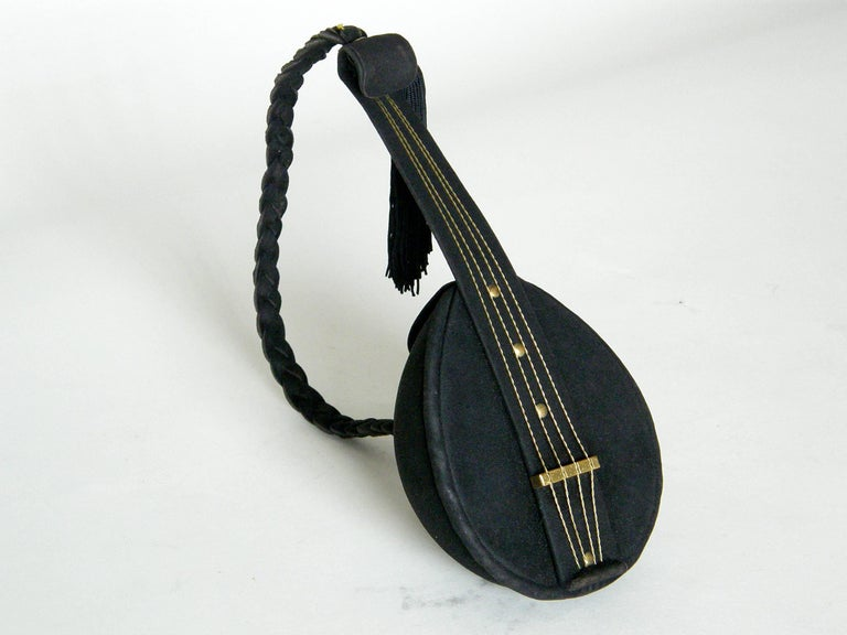 """This delightful figural handbag is shaped like a mandolin. It's covered in a fine, black suede with details and accents in gold plated brass. The """"strings"""" are twisted wires that run through notches in the """"bridge"""". The neck bends slightly and"""