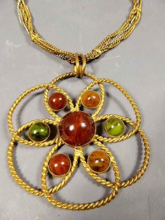 Circa 1970 France  Original Yves Saint Laurent Couture Pendant Necklace by Roger Scemama fromthe Seveenties. Rosace of two gold threads forming a flower. On each petal, stones of khaki green, amber and terracotta based on a golden background. In the