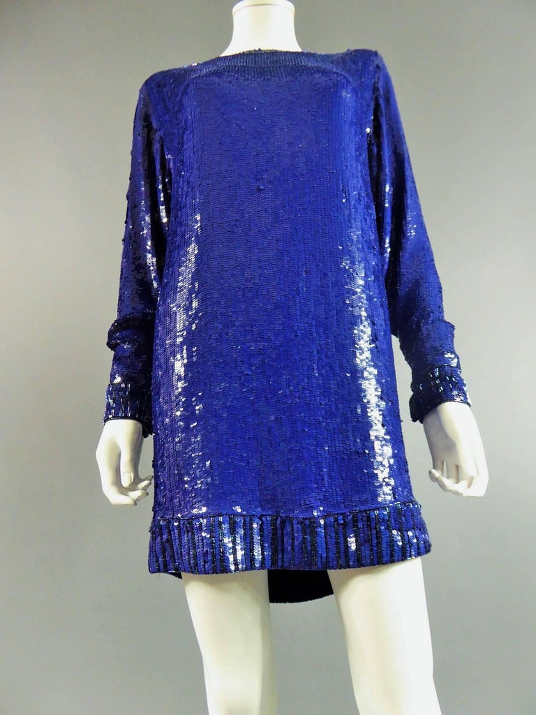 Circa 1980  France  Sweater or sweater dress by Saint Laurent Rive Gauche in majorelle blue color. Sweater dress covered with blue sequins. Collar, sleeves and bottom of the sweater decorated with round and blue tubular and seed beads. Sleeves