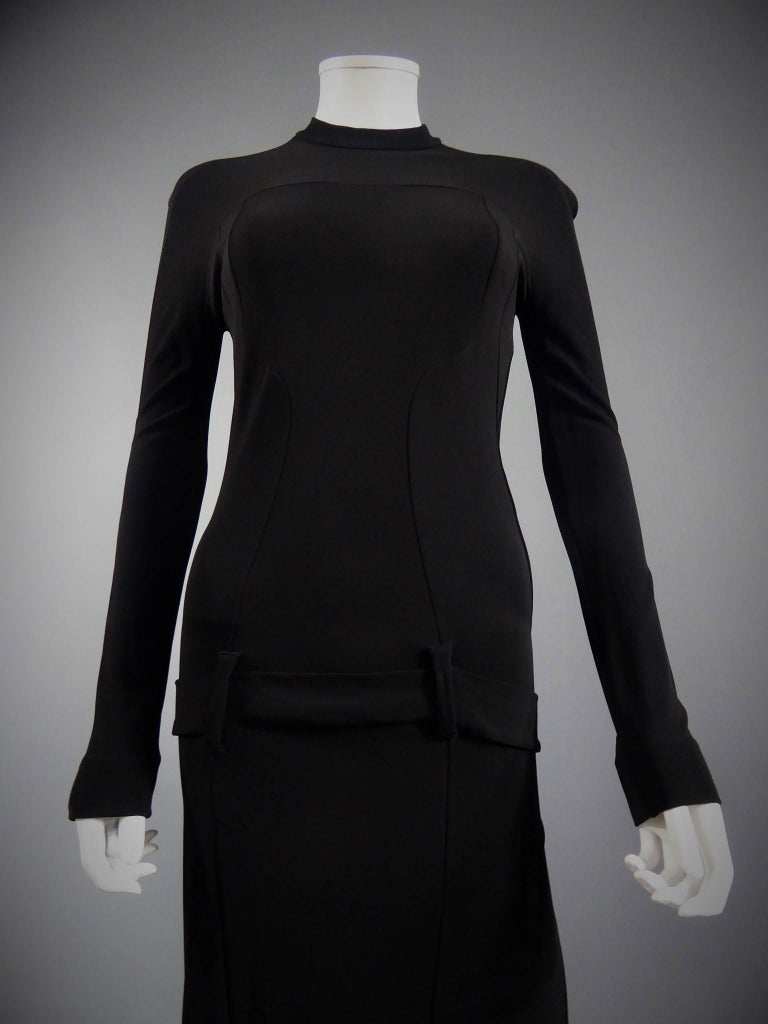 Circa 2000  France  Balenciaga black dress in elastic black jersey. Long sleeves. Nicolas Ghesquière line. Details on the sides, half belt on the front ending at the buttocks. Mid-long skirt under the dress. Zip closure in the back. Very fitted.