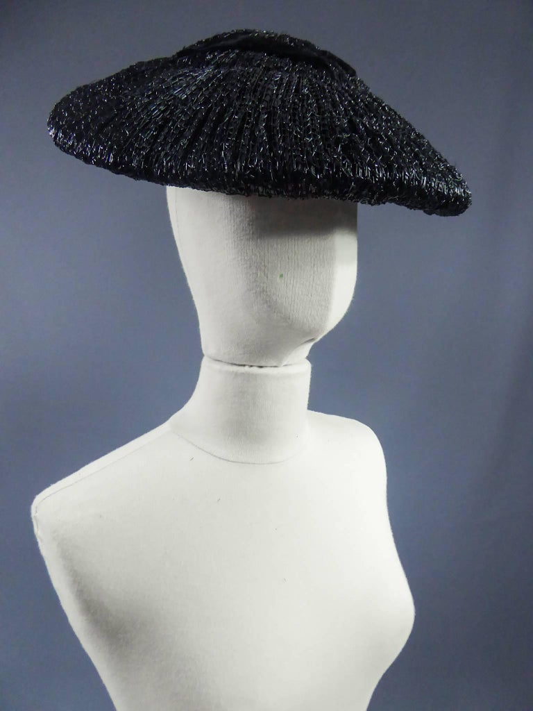 Circa 1947  France  Black straw hat with black velvet ribbon in the style of the New Look era Bar Suit silhouette from 1947. Ribbon inside.  Measurements : largest diameter 36 cm. smallest diameter 35cm. gros grain interior : 15.5 cm.