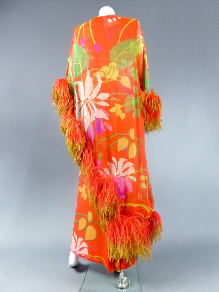 Circa 1975  France  Long tube and cape dress by Pierre Balmain Haute Couture in printed orange chiffon and tropical floral patterns. Sleeve and asymmetric cape similar underlined coral ostrich feathers in lime-green gradient. A nod to the colors and