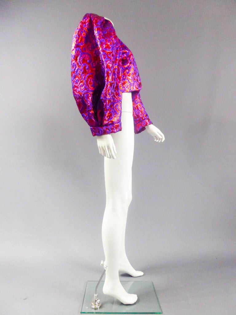 Winter 1989  France  Fuchsia and purple lurex bolero with orange and red highlights, Yves Saint Laurent Haute Couture Winter 1989. Floral patterns in arabesques. Oversized sleeves, fitting sleeves with hollow pleats to the shoulders to give volume