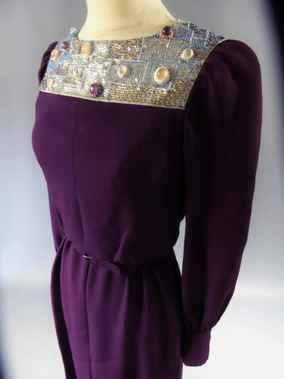 Circa 1970/1975 France  Stunning long dress in crepe silk purple labelled Nina Ricci collection Jeune Femme dating to the 70s. Monastic and futuristic taste fashionable during the 70s thanks to Pierre Cardin or Paco Rabanne. Buttons on the handles