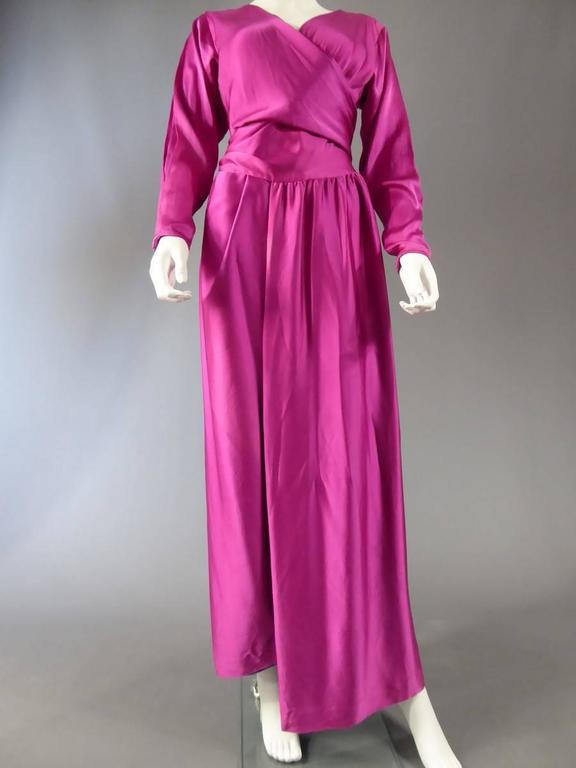 Circa 1970-1980  France  Long evening dress Jeanne Lanvin Numbered 18073. Fuchsia brilliant satin silk 100%. Fully lined with a purple and cream silk dyed by hand closes with a knot in the back with the help of a small size passes .. Very fluid