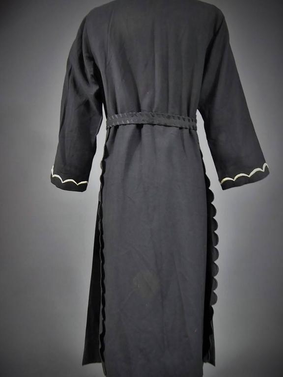 Circa 1920/1930  French Haute Couture  Rare Haute Couture coat or kaftan of evening / interior labelled by Chéruit Wormser and Boulanger, 21 place Vendôme Paris. Black wool serge decorated with white and black embroidered seems . Opening under the