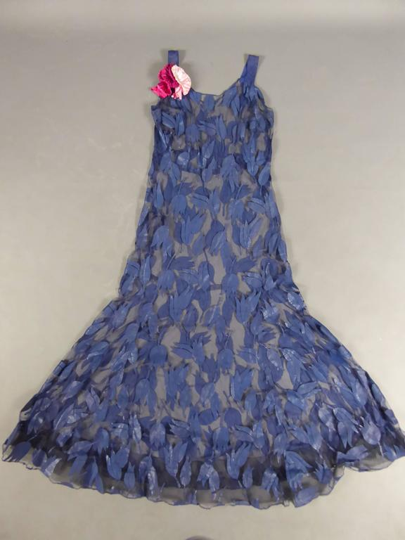 Circa1930 - 1940   France  Deep blue tulle evening dress with tulips appliqué work from the years 1930- 1940. Reinforced bell skirt with a tulle rigid Bolduc for a fallen ruffled . Bouquet of artificial pink flowers on a shoulder. Two leg straps