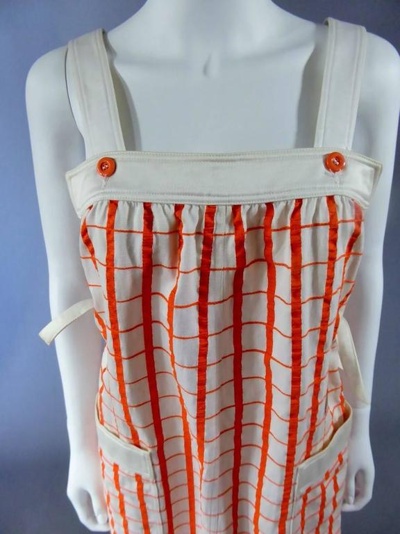 Circa 1965-1970  France A line shape Haute Couture dress by André Courrèges. Model numbered 19055. Attached with two white straps hold by orange buttons on the face and on the back. Pattern of the dress is checkered with orange lines on white