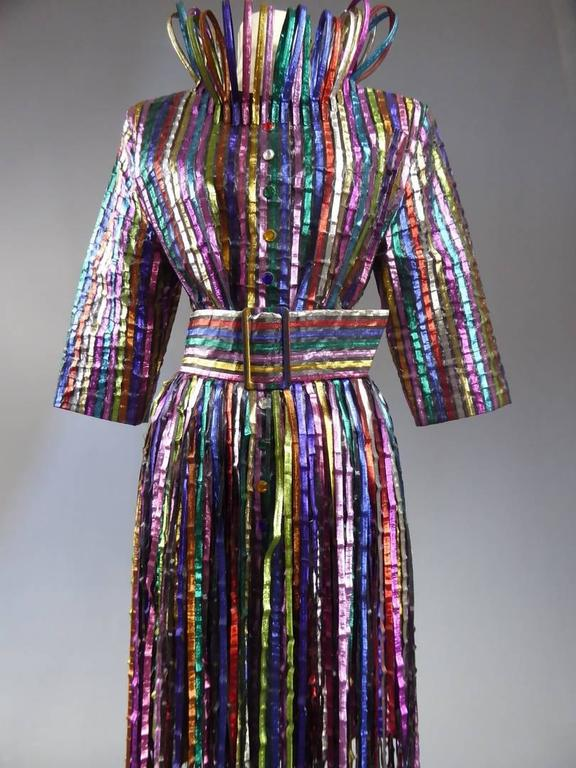 Circa 1992.  France.  Ensemble comprising a long jacket and skirt belted with multicolored iridescent strips looking like the colors of the rainbow. Rigid laminated jacket in similar strips. Button front with multicolored rhinestones. Large and