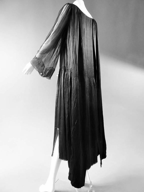 Circa 1920.  France.  Long dress in black silk crepe by Jeanne Lanvin Haute Couture. Wide shape with back of the dress longer than the front. Fitting the skirt, split on the sides on the bottom, with 7 rows of gathers mounted at the front point.