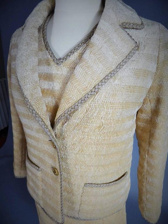 Circa 1970  France  Complete set of six pieces Chanel Haute Couture skirt suit from the 1960s. Chenille knit with brilliant effect, in horizontal stripes composed of chevrons in cream tones. Completely piped with white cord covered with golden