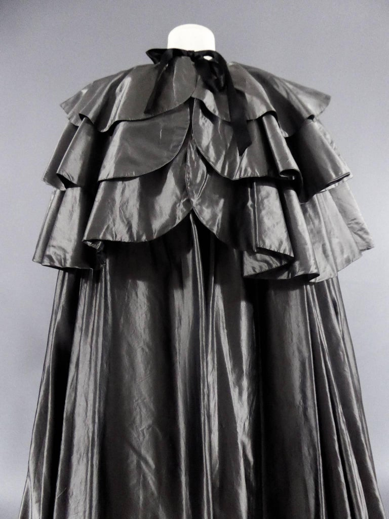 Circa 1975  France  Cape of Princess Lilian of Belgium. Model having been exhibited at the Christian Dior Museum in Granville. Cape of big night way cochet, gray. Hollow-folded and flatter shoulders and three-tiered split-backs. Taffeta silk silver