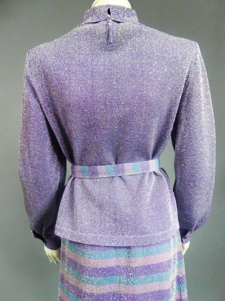 Circa 1980  France  Pierre Balmain three-piece knitwear set in silver and purple lurex. Long-sleeved, tight-fitting top with cuffs. Small turtleneck closing with invisible staples. Long flared skirt with elastic waist, petrol blue stripes, powder