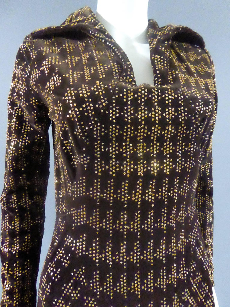 Circa 1975  France  Long dress with loose skirt and brown velvet with golden glitter glued in geometric patterns and houndstooth. Open shirt collar on narrow and rectangular chest. Zipper in the back and collar closed by clasps at the back. Long