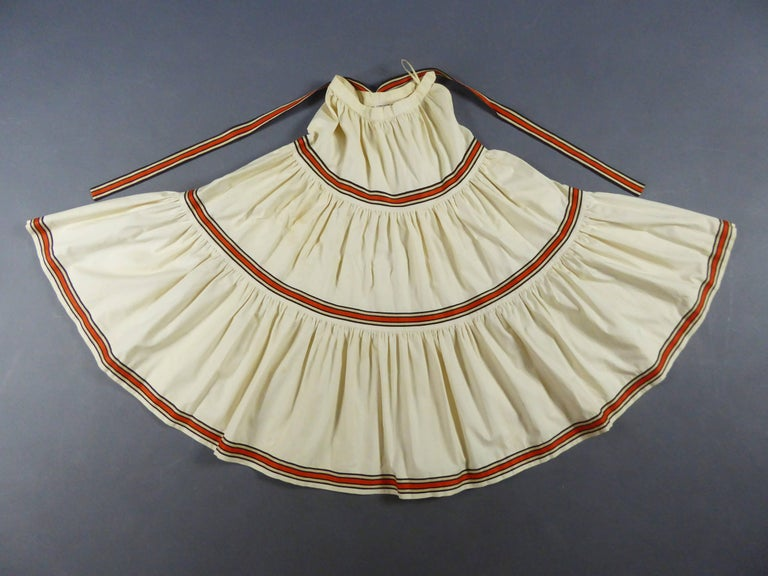 France Paris Circa 1976/1978 An ecru cotton skirt and blouse ensemble by Saint Laurent Rive Gauche. Set inspired by the 1976s  Ballets Russes collection. The blouse has a wide squared low-neck, puffy sleeves tightened at the wrists thank to an