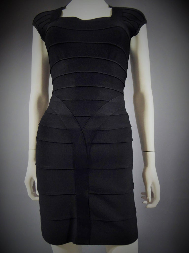 Circa 1990  France  Hervé Léger black mini dress. Bodycon dress withshort sleeves made from an assembly of stretch fabric bands commonly used in the field of lingerie. Square collar, marked size. Very good condition. Size 36 french.  Dimensions: